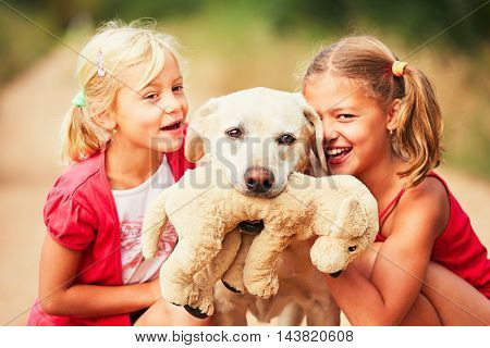 Sisters with dog. Two girls caress yellow labrador retriever with plush toy. - selective focus on the dog