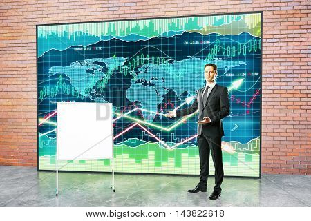 Handsome young fund manage giving presentation with blank flipboard and forex chart on red brick wall background. Mock up poster