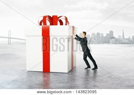 Businessman pushing huge present box on abstract city background. 3D Rendering