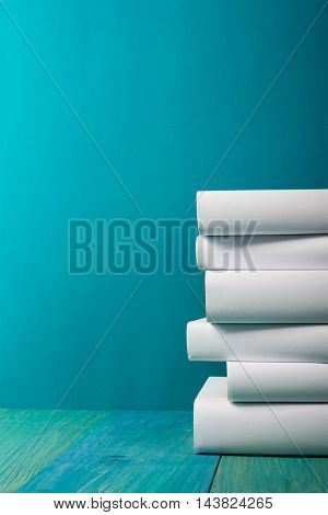 Stack of colorful books, grungy blue background, free copy space Vintage old hardback books on wooden shelf on the deck table, no labels, blank spine. Back to school. Education background