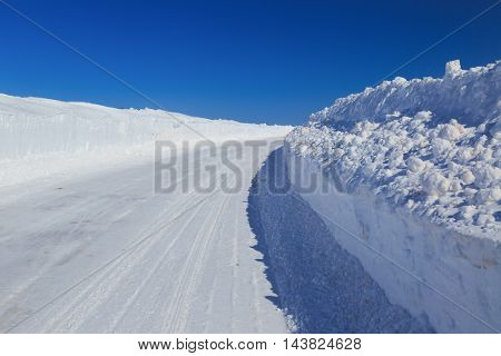 A rural road with high snowbanks on either side.