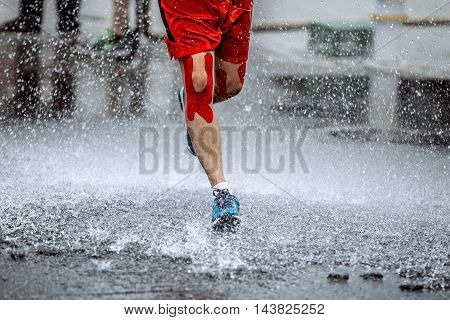 male athlete with tape on his knees running through a puddle of water splashes and drops around feet