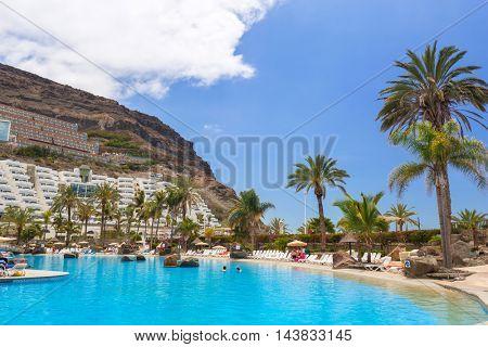 TAURITO, GRAN CANARIA, SPAIN - APRIL 25, 2016: Tourists on sun holidays at the Lago Taurito aquapark in Taurito, Gran Canaria. Taurito is very popular tourist destination