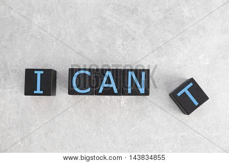 Black cubes with phrase I CANT on light background