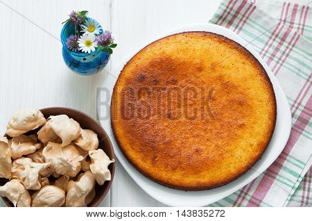 Top view: flowers, brown meringues and manna semolina pie on white wooden table