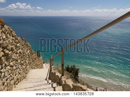 Stone stairs down to azure sea. Steep descent. Rock wall. Blue sparkling water. Costline of Black Sea, Anapa resort, Russia.