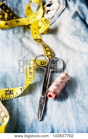 Sewing kit from pink threads, scissor, measuring tape and needle on jeans backround. selective color