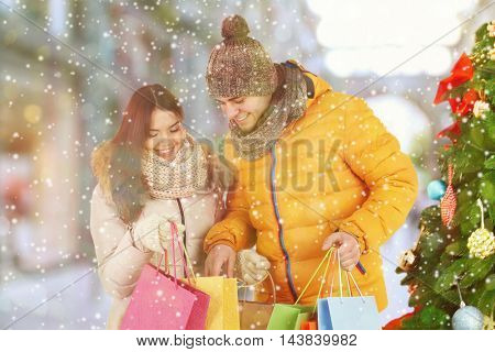 Beautiful couple with colorful bags on blurred city street background. Winter holiday and christmas shopping concept.