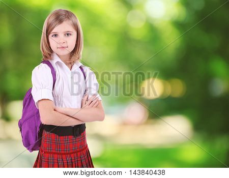 Beautiful little girl with backpack on nature blurred background. Back to school concept