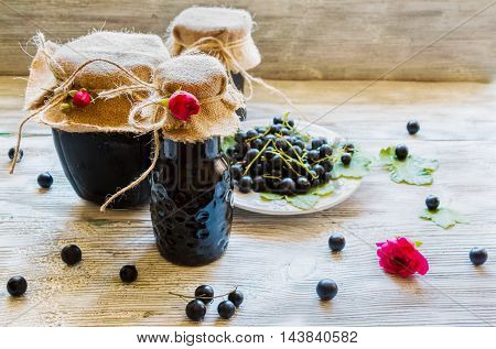 Fresh black currant on white vintage plate and jam in glass jars on wooden background.