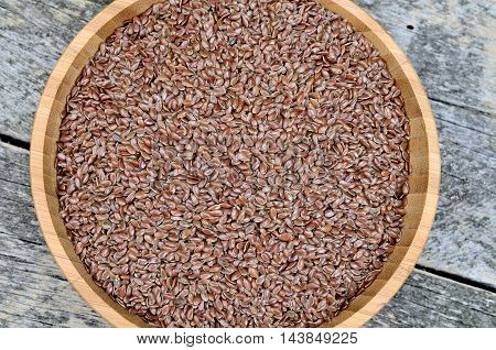 Flaxseed in a bamboo bowl on wooden table
