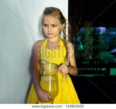 cute girl preparing lemonade in a glass jar