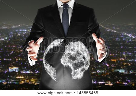 Businessman holding abstract terrestrial globe on illuminated night city background. Global business concept