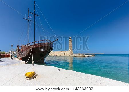 Rethymnon, Island Crete, Greece, - July 1, 2016: View of the harbor with lighthouse and the old sailing ship. Rethymnon is an old historic town on the northern coast of the island Crete.