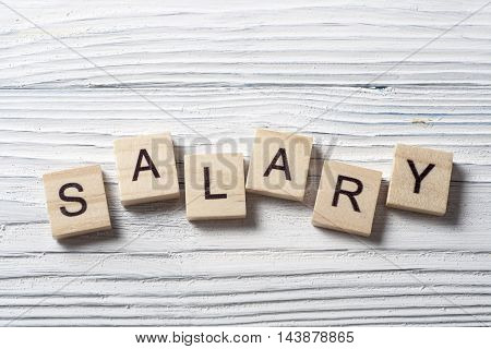 SALARY word written on wood block at wooden background
