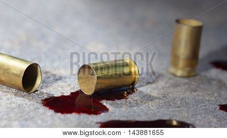 Handgun brass on concrete that has blood pools around