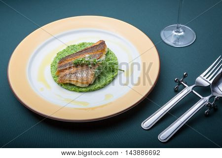 Fried barramundi fish with green vegetables cake on plate in restaurant