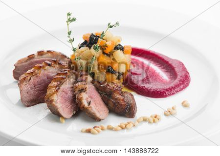Breast of duck magret with fruit gratin and apple sauce on white plate