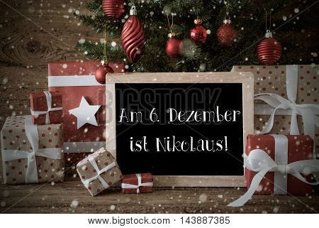 Nostalgic Card For Seasons Greetings. Christmas Tree With Balls And Snowflakes. Gifts In The Front Of Wooden Background. Chalkboard With German Text Am 6. Dezember Ist Nikolaus Means Nicholas Day