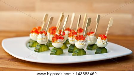 Creamy with red salmon roe skewers and cucumber on white plate background