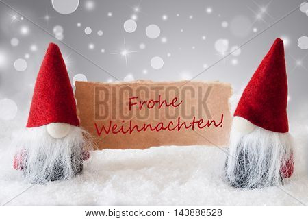 Christmas Greeting Card With Two Red Gnomes. Sparkling Bokeh And Noble Silver Background With Snow. German Text Frohe Weihnachten Means Merry Christmas
