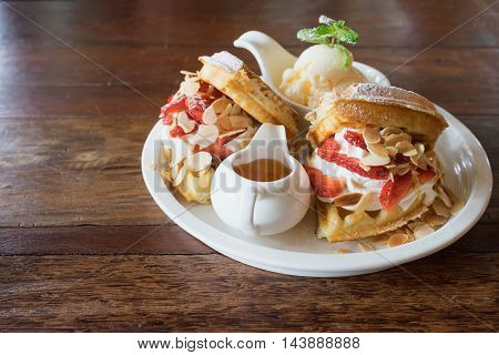 waffle with syrup ice-cream on top with strawberry whip cream on wooden table yummy waffle fresh waffle