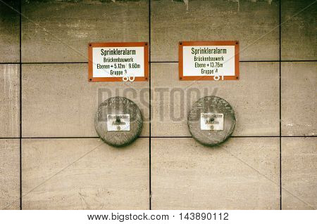 The alarm bells of a sprinkler system with signs on a wall.