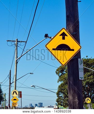 Speed breaker/hump sign on a wooden pole
