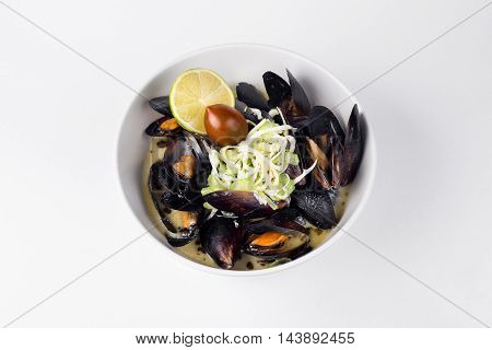 Blue mussels in a creamy sauce with lemon and olive in white bowl