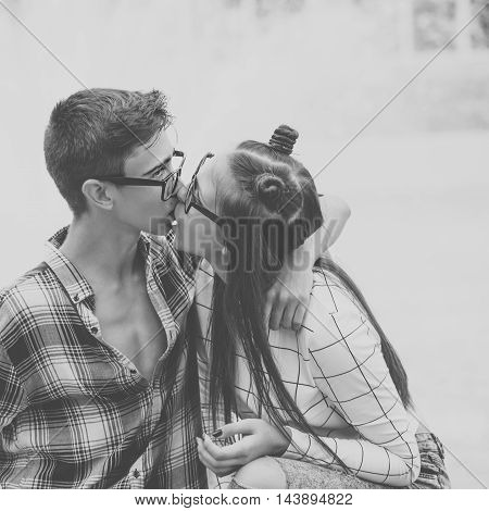 Loving couple kiss teenagers. Girlfriend and boyfriend hugging. They wear glasses. Black and white photography. First love. He falls in love. Date.