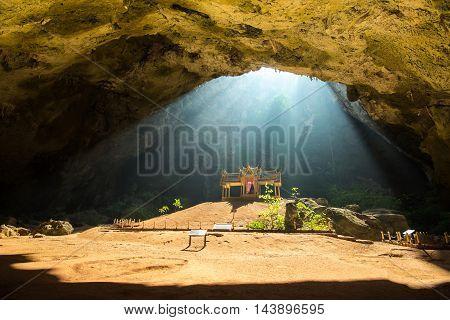 Morning sunbeam on golden buddhist pavilion in wild cave Sam Roi Yot Thailand
