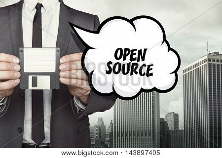 Open Source text on speech bubble with businessman holding diskette