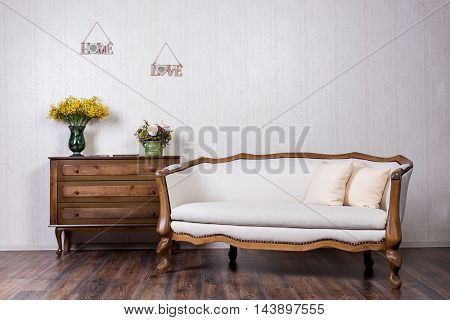 Coach and dresser in home inrerrior decorated with flovers and plates