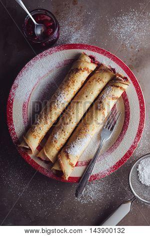 Sugar powdered pancakes with cherry jam