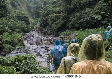 People in raincoat walking in hill in rainy day, selective focus