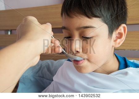 Mother's hand feeding sick kid on the bed