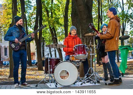Music street performers with girl violinist on autumn outdoor. Group people three men and women with music instrument in park.