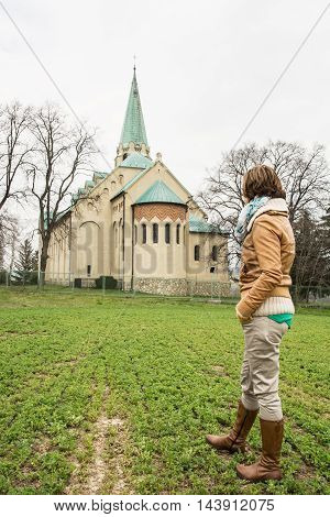 Young caucasian woman posing with parish church of saint Stephen king in Nove Sady village Slovak republic. Rear view. Traveling theme. Vertical composition.