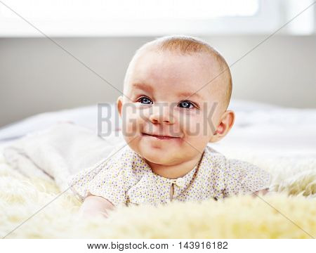 Cute baby on a sheep fur. Beautiful little baby lying on a white bed with selective focus, close-up shot. Smiling baby.