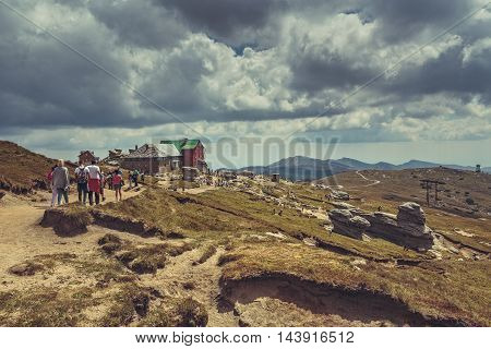 Bucegi Mountains Romania - August 6 2016: Tourists hike the trails to the Babele (The Old Women) chalet at 2206 m altitude in Bucegi Mountains to visit the Babele Rocks and the Sphinx.