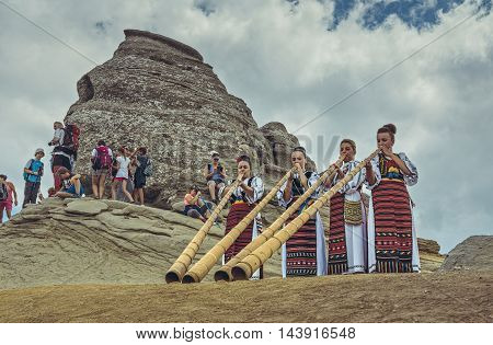 Bucegi Mountains Romania - August 6 2016: Young Romanian women dressed in colorful traditional costumes play the tulnic near the Sphinx megalith in Bucegi mountains.