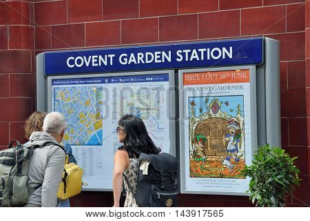 Covent Garden London England United Kingdom - August 16 2016:Tourists looking at map of Covent Garden area at underground station