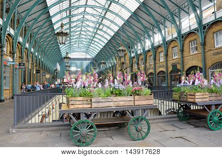 Covent Garden London England United Kingdom - August 16 2016: Central Piazza Convent Garden with Flower Cart in Foreground