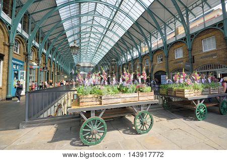 Covent Garden London England United Kingdom - August 16 2016: Central Piazza Convent Garden with Flowers on cart in Foreground