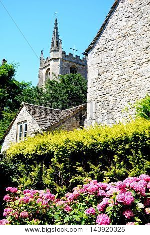 View of St Andrews church tower seen behind a cottage Castle Combe Wiltshire England UK Western Europe.