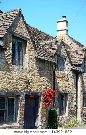 CASTLE COMBE, UNITED KINGDOM - JULY 20, 2016 - Cotswold stone cottage with pretty hanging basket in the village centre Castle Combe Wiltshire England UK Western Europe, July 20, 2016.