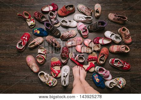 Old worn baby (child kid) shoes on the floor. sandals boots slippers top view.baby feet (legs foot). flat lay poster