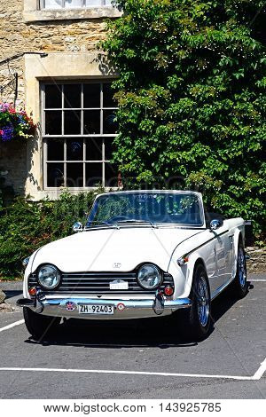 CASTLE COMBE, UNITED KINGDOM - JULY 20, 2016 - A white soft top Triumph TR5 parked in the village Castle Combe Wiltshire England UK Western Europe, July 20, 2016.