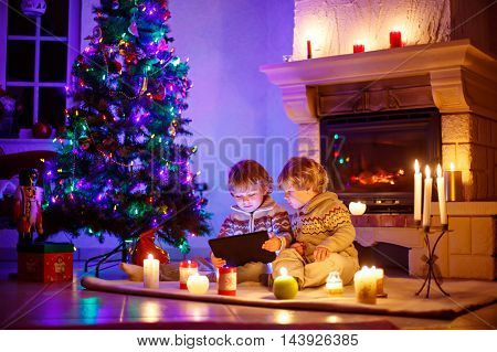 Two little sibling boys sitting by a fireplace at home on Christmas time with a surprise gift. Kids playing with new tablet, with xmas tree, candels and lights.