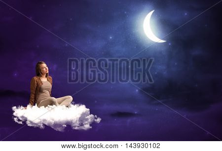 Caucasian woman sitting and wondering on a white cloud, under the moonshine
